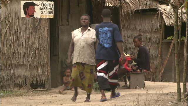 villagers walk past barber's salon in rural village on niger delta, kura region, nigeria - baby boys stock videos & royalty-free footage
