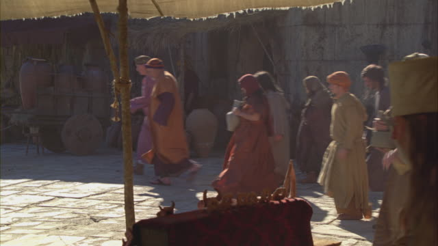 Villagers walking through a marketplace.