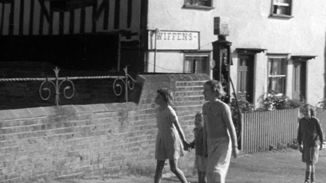 1937 MONTAGE Villagers walking to church / Essex, England