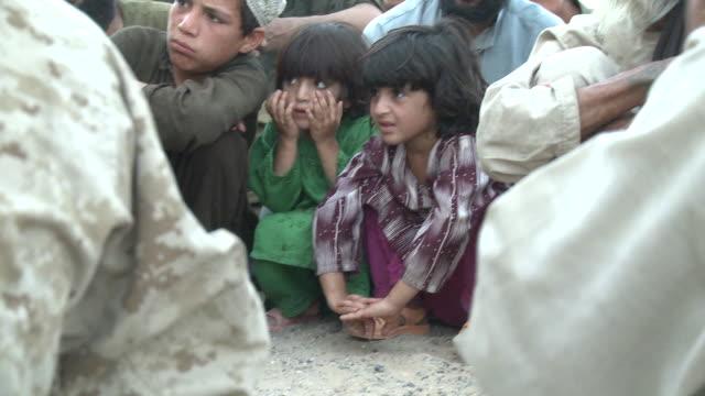 villagers watch a loya jirga in helmand province. - afghanistan stock-videos und b-roll-filmmaterial