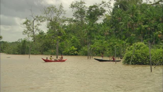 vídeos de stock, filmes e b-roll de villagers wave from their fishing boats on the amazon river. - rio