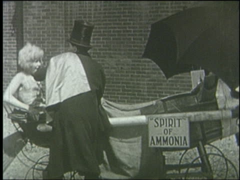 B/W 1920 villain puts woman into flying contraption made of baby buggies + umbrellas