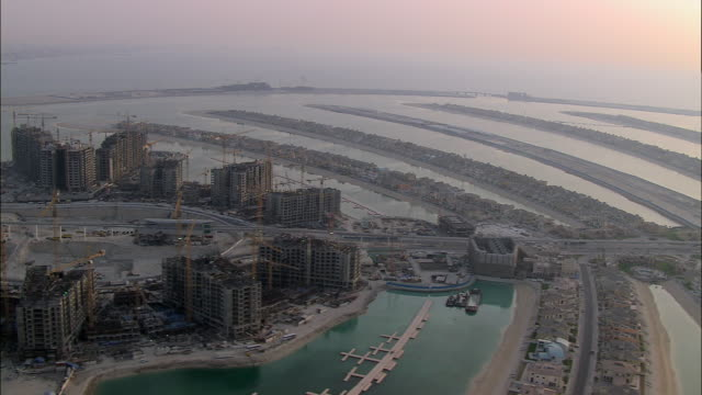 AERIAL Villas on fronds of Palm Jumeirah and buildings under construction, Dubai, United Arab Emirates
