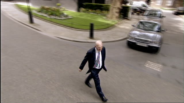 vince cable mp arriving at downing street as greets colleague cable walking along downing street as driver calls him to tell him that he has a car... - downing street stock-videos und b-roll-filmmaterial