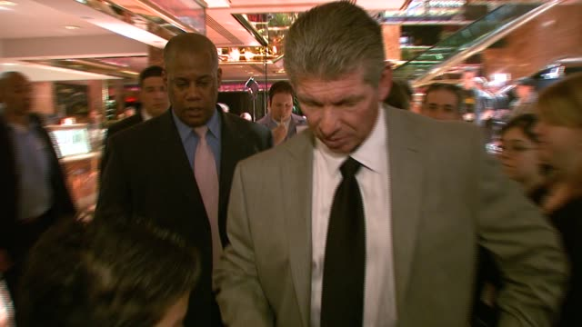 Vince McMahon signs an autograph for a young fan at the Donald Trump and World Wrestling Entertainment News Conference for WrestleMania 23 at Trump...