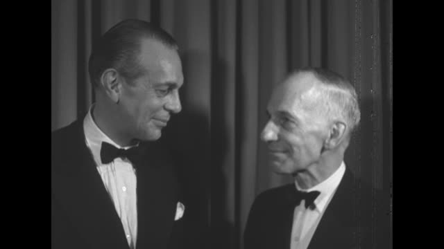 vincent massey and brother raymond massey both in tuxedos talk beside curtain / vincent massey and power, in tuxedo, talk beside curtain / power... - brother点の映像素材/bロール