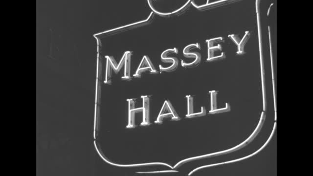vídeos de stock, filmes e b-roll de cu vincent massey in suit and bowtie exits car policeman salutes him flashes go off he walks past bystanders greets person / cu massey hall neon sign... - neckwear