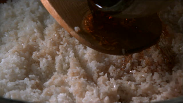 vinegar being put on rice to make sushi in japan - condiments stock videos and b-roll footage