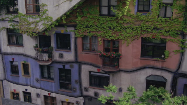 Vines grow up the front of an urban apartment building.