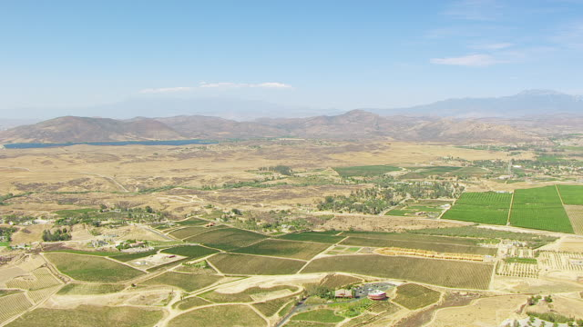 WS AERIAL POV Vineyards and cultivated farmland with Skinner Reservoir and hills in background and with San Bernadino and San Jacinto Mountains in hazy distances / Temecula, California, United States