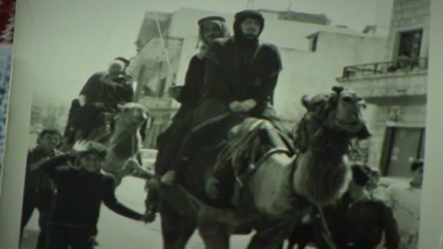 vídeos y material grabado en eventos de stock de vintage 1950s era black and white photograph men riding camels in nabatieh. - imagen virada