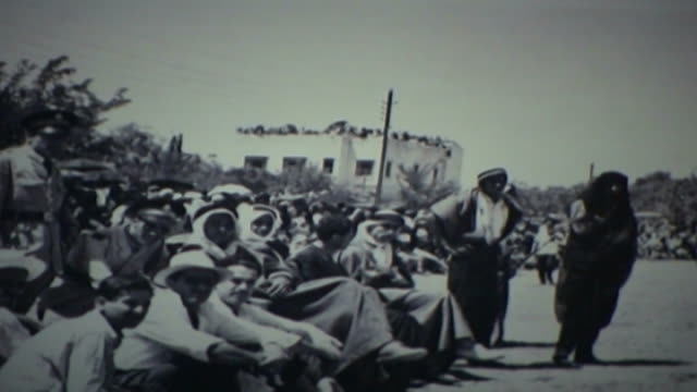 vídeos y material grabado en eventos de stock de vintage 1950s era black and white photograph of ashura commemorations in nabatieh. men in traditional lebanese costumes sitting ins rows waiting for... - ashura