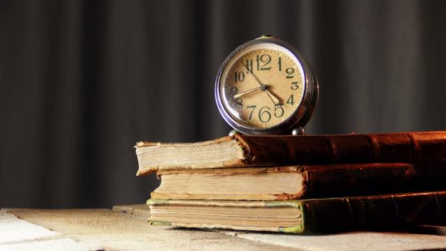 vídeos de stock e filmes b-roll de vintage alarm clock with old leather covere books on wooden table - capa de livro