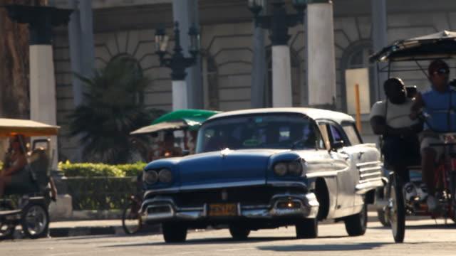 ms of vintage american cars / pedicabs / traffic in havana cuba - fahrradtaxi stock-videos und b-roll-filmmaterial