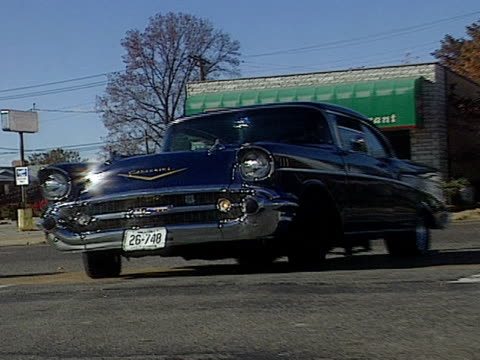 vidéos et rushes de vintage blue and white chevrolet bel air sedan drives down a street and parks in front of ted drewe's frozen custard palace for the route 66 car club... - aller tranquillement