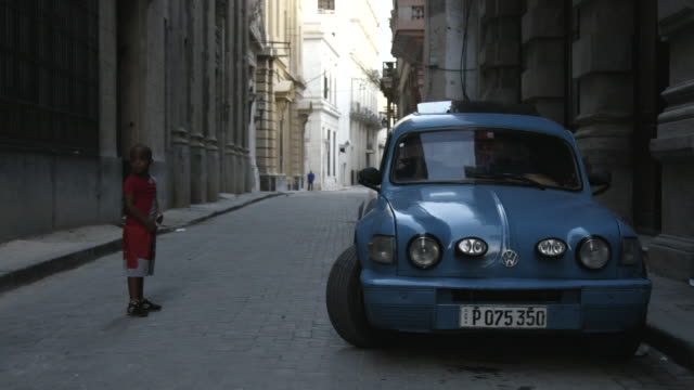 Vintage blue car parked on quiet street in Cuba