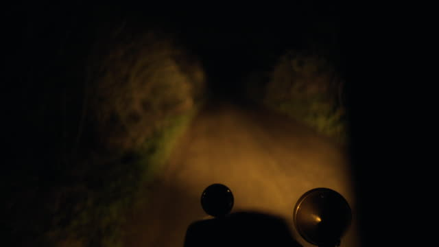 A vintage car drives down a country road at night time