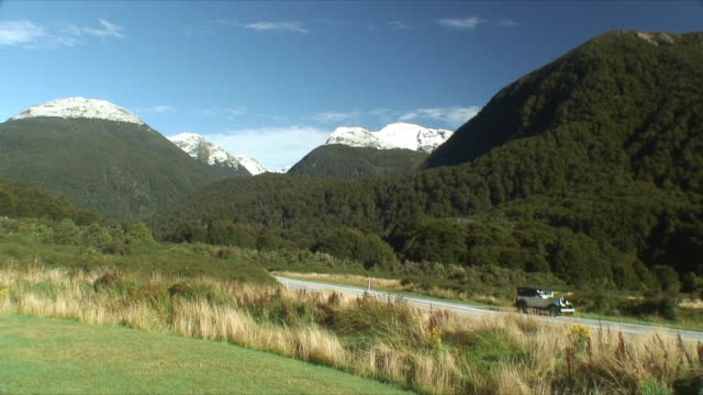 ws vintage car standing by rural road, mt aspiring national park, new zealand - new zealand点の映像素材/bロール