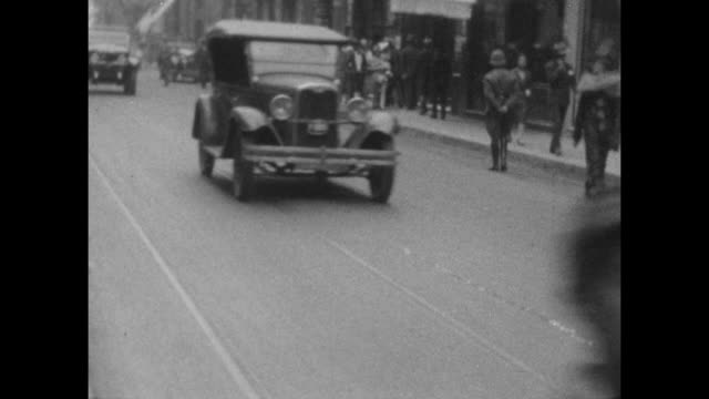 vintage cars drive by as a man dressed as a clown walks past at carnival in buenes aires 1927. - 1920年点の映像素材/bロール