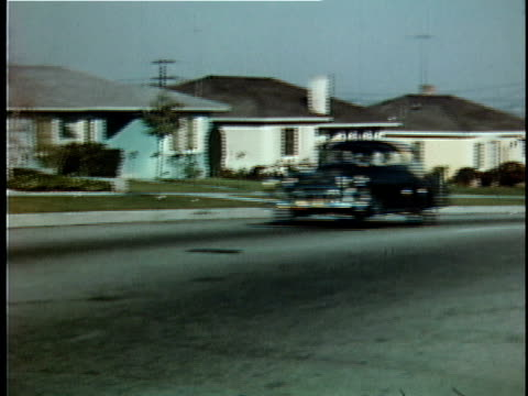 ws pan vintage cars driving down street past suburban houses / usa - 1950 1959 stock videos & royalty-free footage