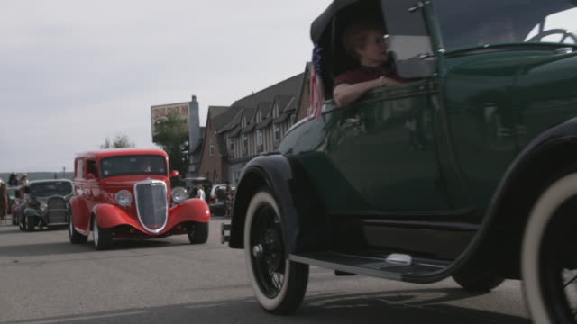 vídeos de stock, filmes e b-roll de ws vintage cars driving in front of lodge / yellowstone, wyoming, usa - hot rod