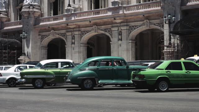 vintage cars driving in street in havana, cuba - stationary点の映像素材/bロール