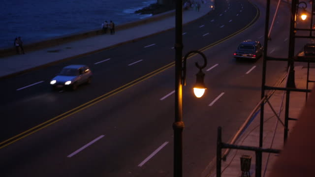 vintage cars driving on malecon during night