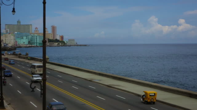vintage cars driving on malecon with hotel nacional in background - hotel nacional stock videos and b-roll footage