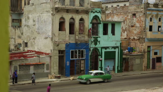 vintage cars passing a building under construction - cuba stock videos & royalty-free footage