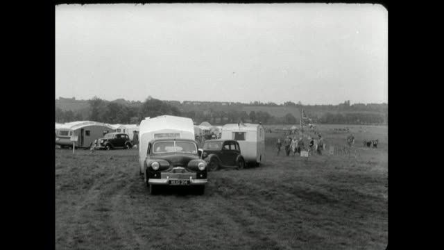 vintage cars tow caravans onto grassy campsite; 1950 - distant stock videos & royalty-free footage