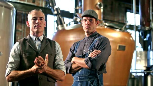 vídeos de stock e filmes b-roll de vintage factory workers in old fashioned distillery - bebida alcoólica
