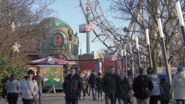 vintage ferris wheel and people in the viennese prater in winter, vienna, austria, europe - プラーター公園点の映像素材/bロール