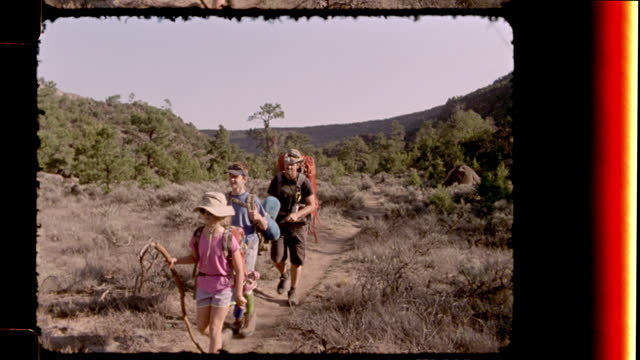 vintage film camera captures family backpacking along rugged trail at rio grande del norte national monument on new mexico camping trip. - nostalgie stock-videos und b-roll-filmmaterial