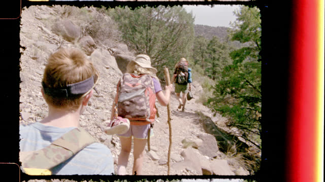 vintage film camera follows family backpacking along rocky trail at rio grande del norte national monument on new mexico hiking trip. - nationalpark stock-videos und b-roll-filmmaterial