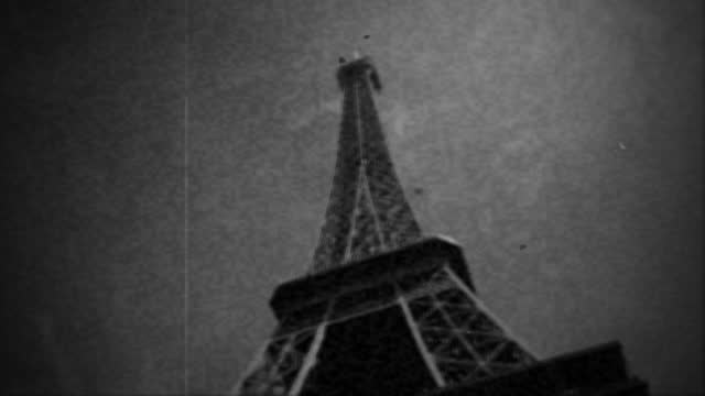 vintage film footage looks up at the eiffel tower as a bird flies by overhead on sunny day in paris. - newsreel stock videos & royalty-free footage