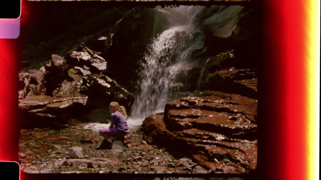 Vintage film footage of a girl sitting below a beautiful waterfall and walking along the pebbles in the stream.