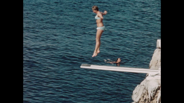 Vintage home movie footage from Cannes in the South of France circa August 1960 / Young woman jumping into the sea from a diving board