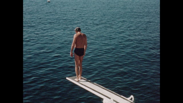 Vintage home movie footage from Cannes in the South of France circa August 1960 Mature man jumping into the sea from a diving board