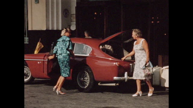 Vintage home movie footage from Cannes in the South of France circa August 1960 Red sports car being loaded outside hotel with three ladies posing...