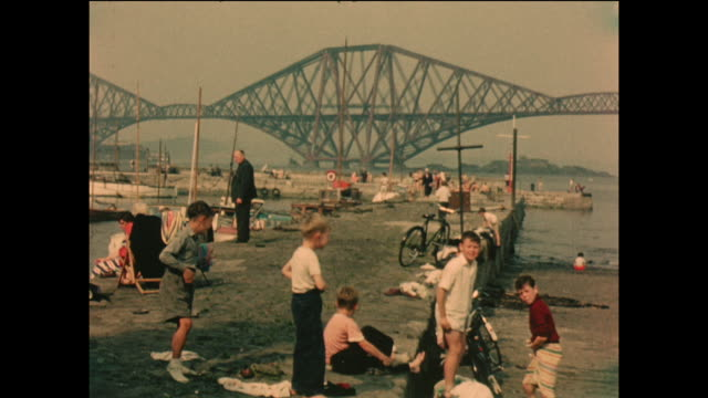 vintage home movie footage of children enjoying the sun on the banks of the firth of forth, edinburgh with the forth railway bridge beyond, circa... - cantilever bridge stock videos & royalty-free footage