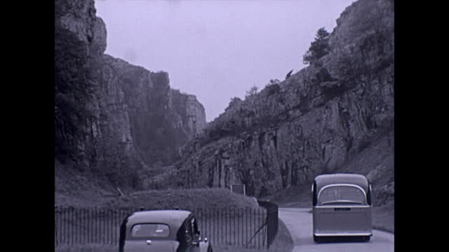 vintage lorry drives down cheddar gorge followed by a coach and car. pedestrians walk towards the camera / pan up the gorge archival - cheddar gorge stock videos & royalty-free footage