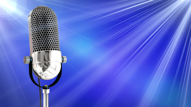 Vintage microphone on microphone stand with blue background