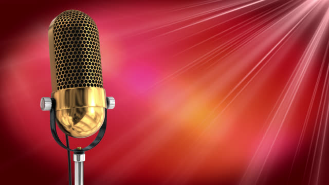Vintage microphone on microphone stand with red background
