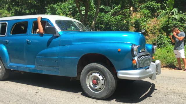 a vintage obsolete car drives in the dirt road to the amazement of the tourist 'topes de collantes' in the cuban province of sancti spiritus is a... - sancti spiritus province stock videos and b-roll footage