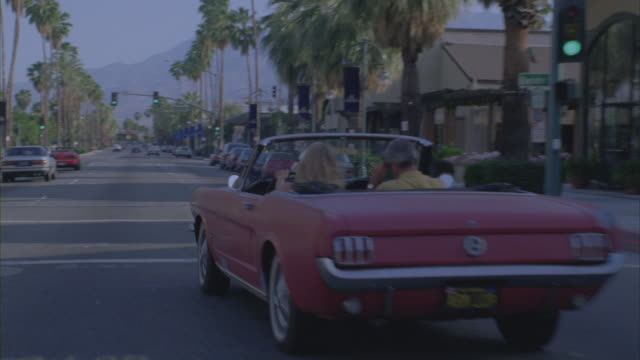 A vintage pink Ford Mustang convertible zooms down a palm tree-lined city street.