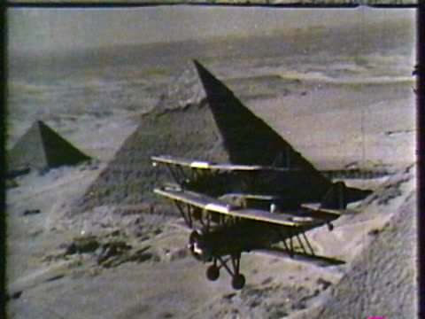 Vintage planes flying by pyramids