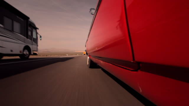 a vintage red convertible merges onto on a highway behind a motor home. - overtaking stock videos and b-roll footage