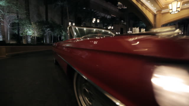a vintage red convertible parks under the portico of the palazzo entrance in las vegas, nevada. - the palazzo las vegas stock videos & royalty-free footage