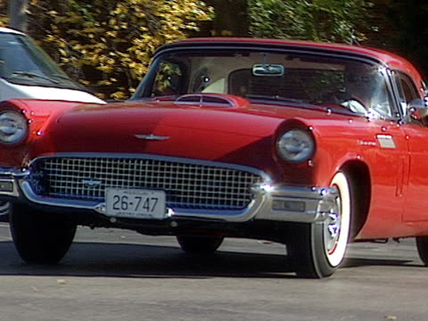 vidéos et rushes de vintage red thunderbird hardtop drives down a street on a windy day in st. louis and then backs into a parking spot. - aller tranquillement