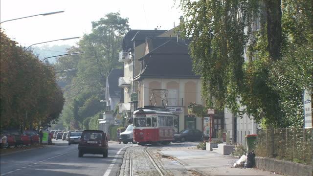 vintage red tram travels alongside traffic on busy street before turning into sideroad - オーストリア点の映像素材/bロール